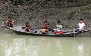দল বেধে নদীতে বড়শি দিয়ে মাছ ধরতে ব্যস্ত দুরন্ত শিশুরা। ছবি- বিবার্তা২৪.নেট